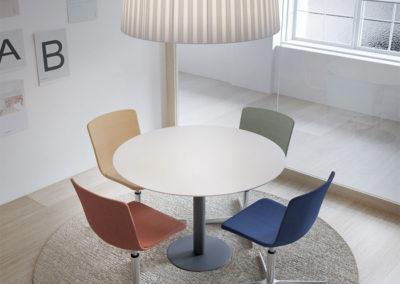salle de réunion meublée d'une table ronde et de sièges ergonomiques dans une ambiance moderne