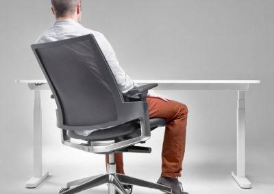fauteuil de bureau ergonomique avec roulettes et accoudoirs, gris, en situation avec dossier inclinable, avec un homme assis et devant un bureau
