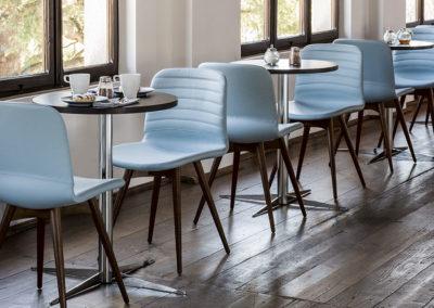 salle de déjeuner avec plusieurs tables rondes et sièges bleu et bois dans un esprit moderne et chaleureux, parquet au sol